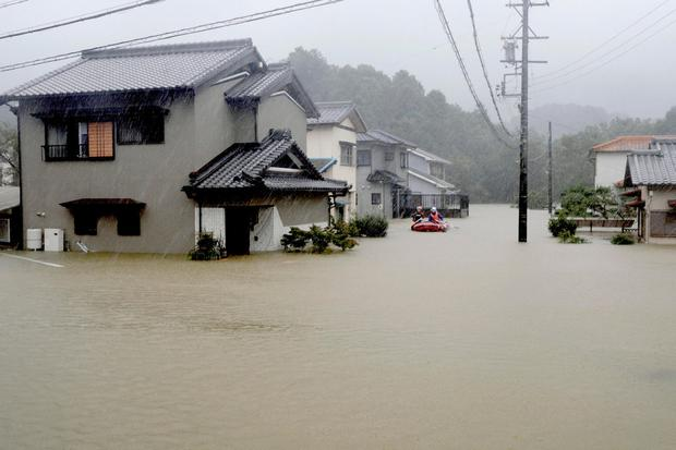 Rescuers on a boat patrol the residential area flooded by Typhoon Hagibis, in Ise, central Japan Saturday, Oct. 12, 2019. (Kyodo News via AP)