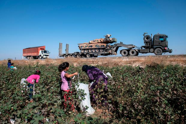 Turkish military vehicles carrying tanks head to the Syrian border as farmers work in a cotton field on October 12, 2019 in Akcakale, Turkey. Photo by Burak Kara/Getty Images