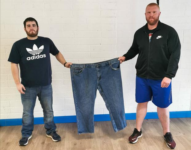 'Phenomenal': Jason (left) – 17st lighter – with trainer Davy Jones and his old 58in jeans. Photo: Ciara Wilkinson