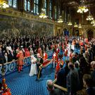 Queen Elizabeth II, accompanied by the Prince of Wales, proceed through the Royal Gallery before delivering the Queen's Speech during the State Opening of Parliament in the House of Lords at the Palace of Westminster in London. PA Photo