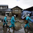 Workers walk past homes destroyed by Typhoon Hagibis in Nagano, Japan (AP Photo/Jae C. Hong)