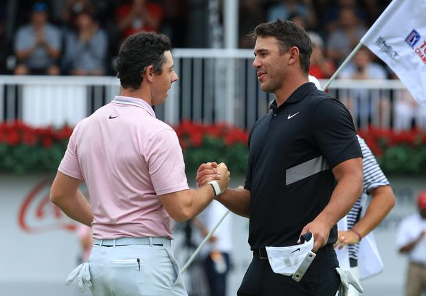 Brooks Koepka of the United States congratulates Rory McIlroy of Northern Ireland on the 18th green after McIlroy won the FedEx Cup and Tour Championship during the final round of the TOUR Championship at East Lake Golf Club on August 25, 2019 in Atlanta, Georgia. (Photo by Streeter Lecka/Getty Images)