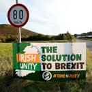 Tension: Motorists pass an anti-Brexit Irish Unity banner after crossing the border into Dundalk, from Newry in Northern Ireland. Picture: AFP/Getty
