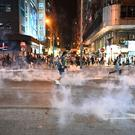 People react from tear gas fired by police at Mongkok during a pro-democracy rally in Kowloon district in Hong Kong (Photo by Philip FONG / AFP)