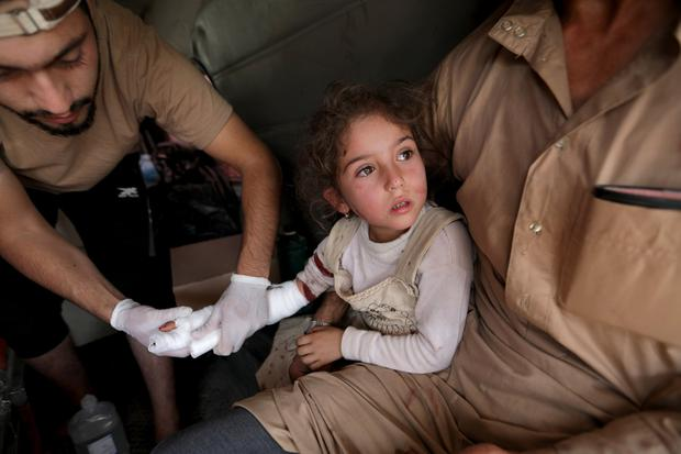 Injured child: A wounded girl is treated by Syrian rebel fighters in the town of Tal Abyad, near where US forces are decamping in Syria. Photo: REUTERS/Khalil Ashawi