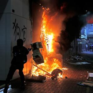 Protesters set fire to a Xiaomi shop in Hong Kong. Hong Kong protesters again flooded streets on Sunday, ignoring a police ban on the rally and setting up barricades amid tear gas and firebombs. AP Photo/Kin Cheung