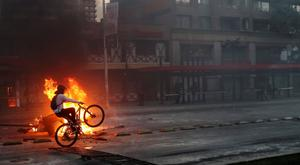 Damage: A protester rides past a street bonfire in Santiago. Photo: REUTERS/Ivan Alvarado