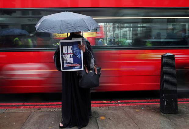 A demonstrator holds a placard during a protest outside of Westminster Magistrates Court, where a case management hearing in the U.S. extradition case of WikiLeaks founder Julian Assange is held, in London, Britain, October 21, 2019. REUTERS/Hannah McKay