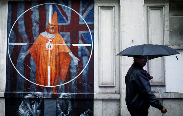 A man walks past an artwork depicting WikiLeaks founder Julian Assange on a building near Westminster Magistrates Court, where a case management hearing in Assange's U.S. extradition case is held, in London, Britain, October 21, 2019. REUTERS/Henry Nicholls