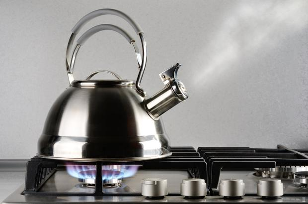 Tea kettle with boiling water on gas stove
