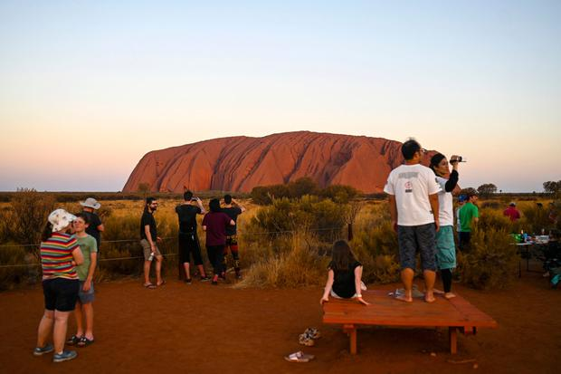 In this Oct. 10, 2019, photo, tourists view the sandstone monolith called Uluru that dominates Australia's arid center at Uluru-Kata Tjuta National Park. (Lukas Coch/AAP Image via AP)