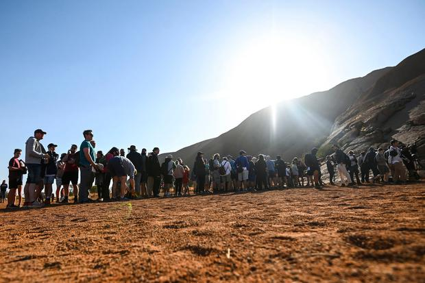 Tourists line up waiting to climb the sandstone monolith called Uluru that dominates Australia's arid center at Uluru-Kata Tjuta National Park, Friday, Oct. 25, 2019 (Lukas Coch/AAP Image via AP)