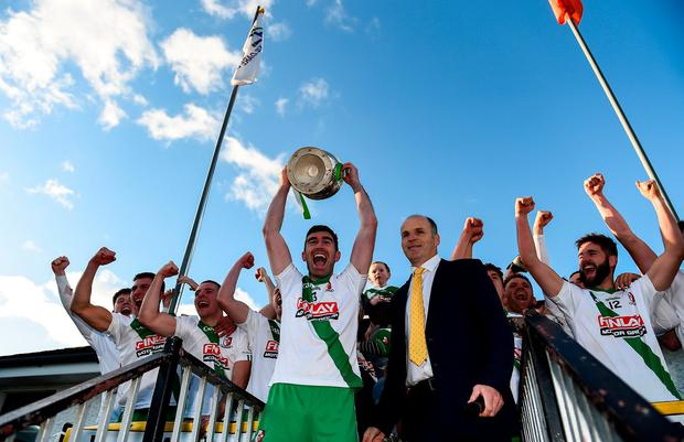 Seán Campbell lifts the cup for Sarsfields at St Conleth's Park in Newbridge. Photo: Eóin Noonan/Sportsfile
