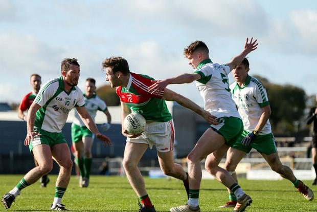 Michael Monaghan of Garrycastle looks for a way out of the Emmet Óg defence. Photo: Michael P Ryan/Sportsfile