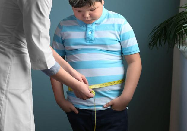 Doctor measuring overweight boy in clinic. Stock picture