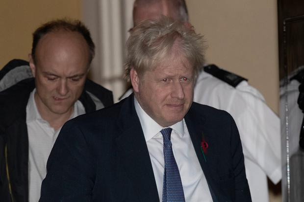 British Prime Minister Boris Johnson and his advisor Dominic Cummings, left, leave 10 Downing Street in London, and get in a car together to go to the Houses of Parliament, on Monday, October 28, 2019. (AP Photo/Matt Dunham)