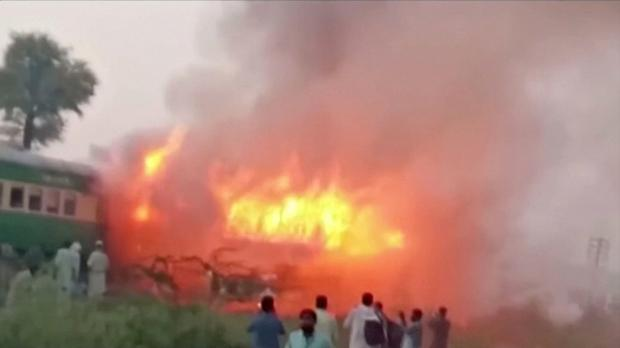 People watch fire burning a train after a gas canister passengers were using to cook breakfast exploded, near the town of Rahim Yar Khan in the south of Punjab province, Pakistan October 31, 2019, in this still image take from video. Picture: REUTERS/Asghar Bhawalpuri/via REUTERS TV