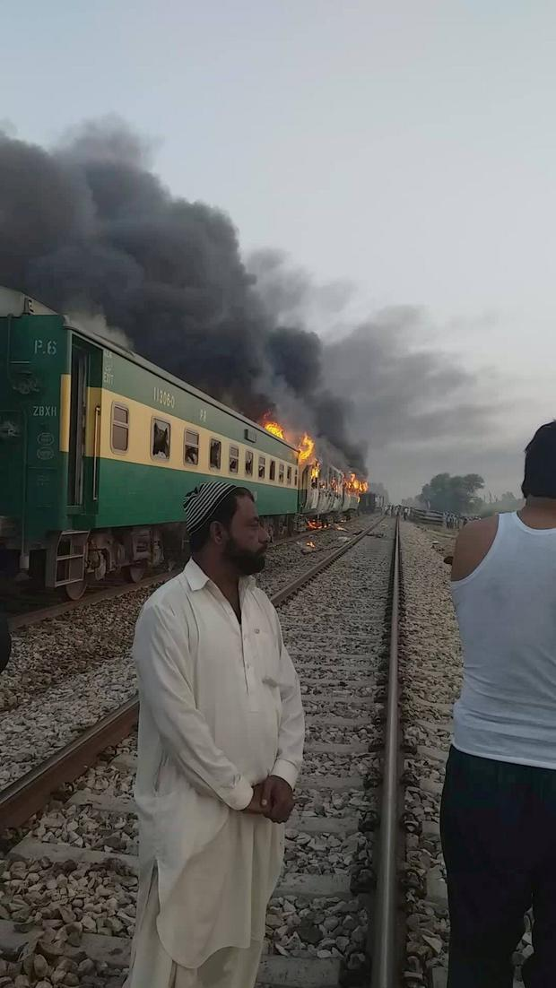 A man stands in front of a burning train after a gas canister passengers were using to cook breakfast exploded in this still image take from video obtained from social media. Picture: Jawedasrar Siddiqui via REUTERS