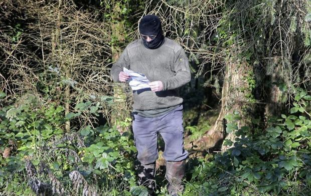 Threat: A masked man was photographed with a statement threatening directors of Quinn Industrial Holdings
