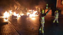 Cars alight and a downed lamp post blocking the entrance to an estate in Fortunestown. Photo Dublin Fire Brigade/Twitter