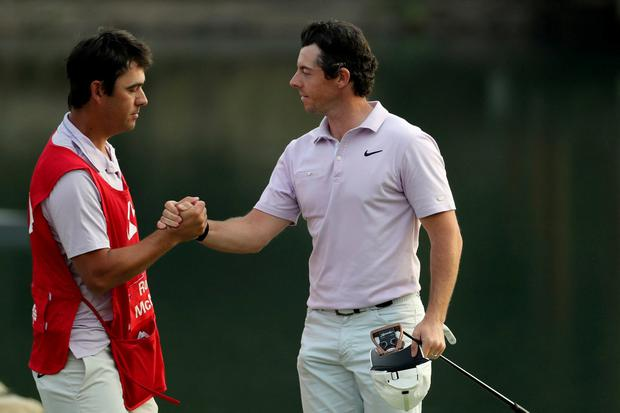 Rory McIlroy of Northern Ireland shakes hands with his caddy after finishing the 18th hole during day three of the HSBC Champions golf tournament held at the Sheshan International Golf Club in Shanghai on Saturday, Nov. 2, 2019. McIlroy spun a wedge down to 3 feet for birdie on his final hole for a clean card at a 5-under 67, giving him a one-shot lead over Louis Oosthuizen on a Saturday of big runs and ugly collapses. (AP Photo/Ng Han Guan)