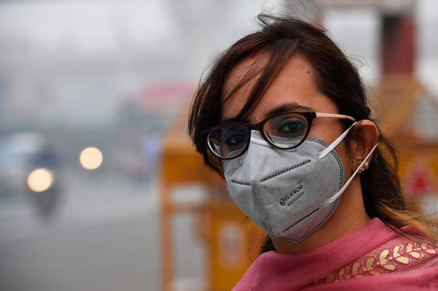 A woman wearing a protective face mask waits for public bus in smoggy conditions in New Delhi (Photo by PRAKASH SINGH/AFP via Getty Images)