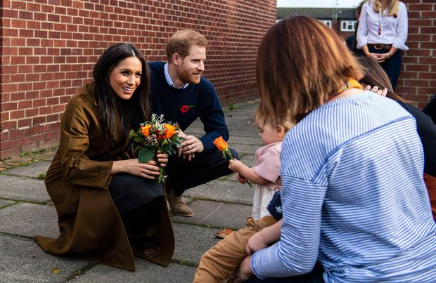 Handout photo dated 06/11/19 issued by MoD showing the Duchess of Sussex receiving a posy of flowers from Bonnie and Maggie Emanuel (mother and daughter), during a visit to Broom Farm Community Centre in Windsor