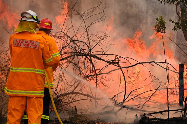 Firefighters tackle a bushfire to save a home in Taree, 350km north of Sydney on November 9, 2019 as they try to contain dozens of out-of-control blazes that are raging in the state of New South Wales. (Photo by PETER PARKS / AFP) (Photo by PETER PARKS/AFP via Getty Images)