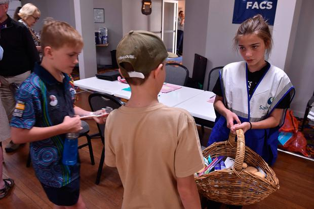 Children help distribute toothbrushes and amenities as residents take refuge at a local club in Taree, 350km north of Sydney on November 9, 2019, as firefighters try to contain dozens of out-of-control blazes that are raging in the state of New South Wales.
