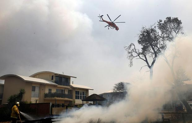 A fire bombing helicopter works to contain a bushfire along Old Bar road in Old Bar, New South Wales, Australia November 9, 2019. AAP Image/Shane Chalker/via REUTERS