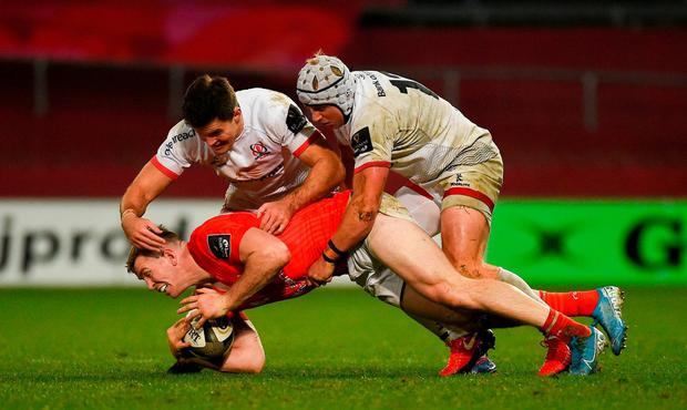 Chris Farrell of Munster is tackled by Jacob Stockdale and Luke Marshall of Ulster. Photo: Diarmuid Greene/Sportsfile