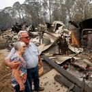 Lyn and Peter Iverson with their burnt out office and shed on their property at Half Chain road, Koorainghat, Australia, November 11, 2019. AAP Image/Darren Pateman/via REUTERS