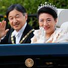 Japans Emperor Naruhito (L) and Empress Masako (R) wave during a royal parade in Tokyo on November 10, 2019