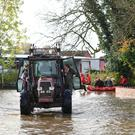 A tractor transports residents through floodwater in Fishlake, Doncaster as parts of England endured a month's worth of rain in 24 hours, with scores of people rescued or forced to evacuate their homes. PA Photo