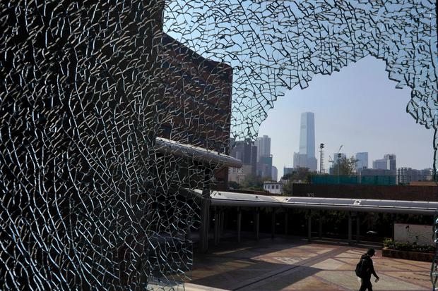 A protester walks by a broken window on the campus of the Hong Kong Polytechnic University, in Hong Kong, Wednesday, Nov. 13, 2019. Photo: AP Photo/Vincent Yu
