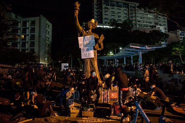 Protesters sit next to a Goddess of Democracy statue at the Chinese University of Hong Kong (CUHK) in Hong Kong on November 12, 2019. Photo: DALE DE LA REY / AFP