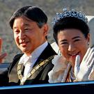 Japanese Emperor Naruhito, left, and Empress Masako, right, wave during the royal motorcade in Tokyo, Sunday, November 10, 2019. Photo: AP Photo/Eugene Hoshiko