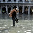 A man carries a woman on his back through the flooded St. Mark's Square during a period of seasonal high water in Venice, Italy, November 14, 2019. REUTERS/Flavio Lo Scalzo TPX IMAGES OF THE DAY