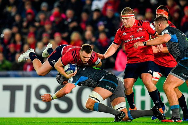 Flying high: Munster centre Rory Scannell is tackled by Dan Lydiate of Ospreys during Saturday's clash in the Liberty Stadium. Photo: Seb Daly/Sportsfile