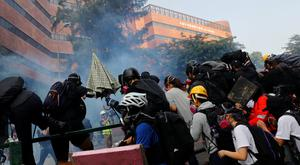 Protesters run from tear gas as they try to re-enter the campus of Hong Kong Polytechnic University (PolyU) after a failed attempt to leave, during clashes with police in Hong Kong, China November 18, 2019. REUTERS/Thomas Peter