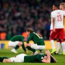 Ireland captain Shane Duffy can't hide his frustration at the final whistle as Denmark players celebrate their Euro 2020 qualification after last night's 1-1 draw. Photo: Stephen McCarthy/Sportsfile