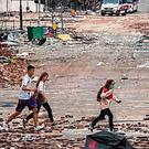 Runaway: Students rush through the streets covered in debris. Photo: Nicolas Asfouri/AFP via Getty Images