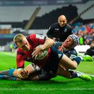 Munster's Keith Earls of Munster dives over to score his side's second try, despite the tackle of Hanno Dirksen of Ospreys, during the Heineken Champions Cup Pool 4 Round 1 match at Liberty Stadium in Swansea, Wales. Photo: Seb Daly/Sportsfile