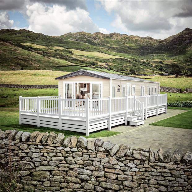 The elegant ABI Beaumont is a boutique hotel-style mobile home painted in cappuccino and white with double-glazed French doors and an outdoor deck