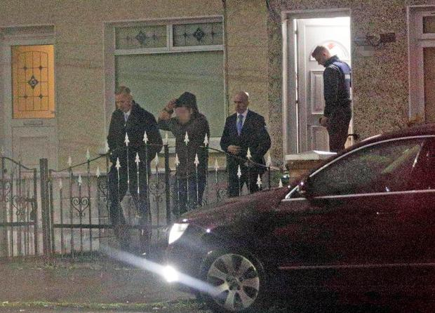 Gardai arrest a 38-year-old man during a dawn raid in the East Wall area. Photo: Mick O'Neill