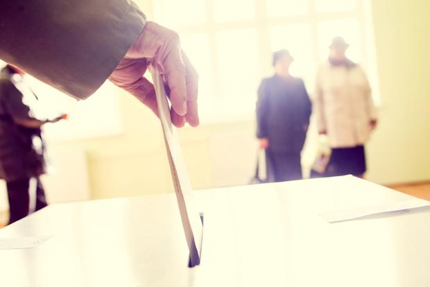 Hand of a person casting a ballot at a polling station during voting. Stock image