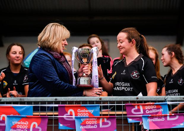 24 November 2019; Eileen Lyons of Donoughmore receives the Cup from Marie Hickey, LGFA President, following the All-Ireland Ladies Junior Club Championship Final match between Donoughmore and MacHale Rovers at Duggan Park in Ballinasloe, Co Galway. Photo by Harry Murphy/Sportsfile