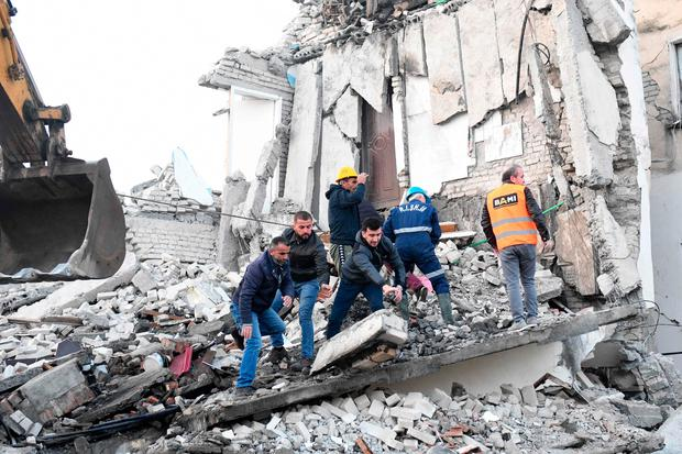 Emergency workers clear debris at a damaged building in Thumane (Photo by GENT SHKULLAKU/AFP via Getty Images)