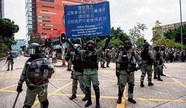 Protest: Riot police arrive to disperse protesters during a lunch break rally in the Kowloon Bay area yesterday. Photo: Nicolas Asfouri/AFP/Getty