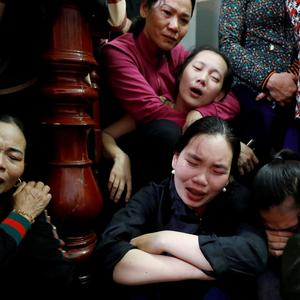Relatives of John Hoang Van Tiep, a victim who was found dead in the back of a British truck last month, mourn near his coffin during his funeral at home in Nghe An province, Vietnam November 27, 2019. REUTERS/Kham